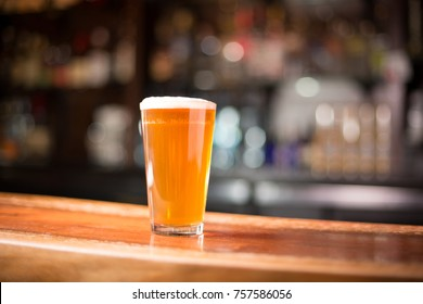Low angle close up of traditional tumbler pint beer glass filled with golden malt and hoppy India pale ale with foam head on wood counter top bar with blurry restaurant background