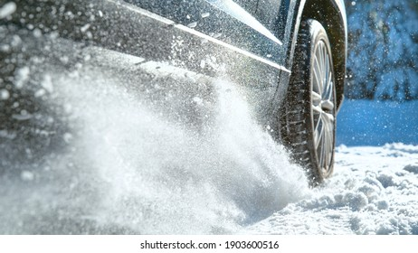 LOW ANGLE, CLOSE UP, DOF: Fresh snow flies up from a large vehicle's spinning wheel. Car's wheels spin and spew up pieces of snow and snowflakes as it attempts to gain traction on the slippery road.