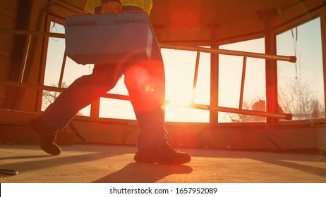 LOW ANGLE, CLOSE UP, LENS FLARE: Worker coming to work carries his metal toolbox and ladder across the room on a sunny morning. Builder leaves the construction site at picturesque golden sunset.