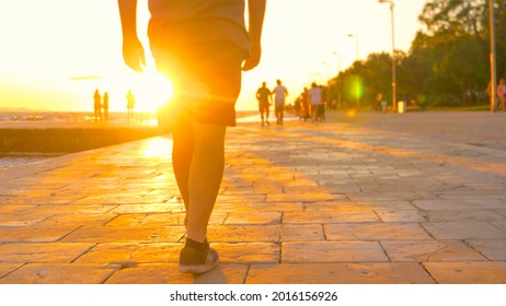 LOW ANGLE, CLOSE UP, LENS FLARE, DOF: Man strolls along the golden lit Croatian coast. Unrecognizable male tourist in shorts and sneakers walks along the Zadar promenade on a sunny summer evening.