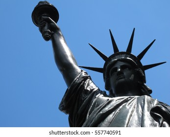 Low angle closeup of the Liberty Statue, blue sky at background