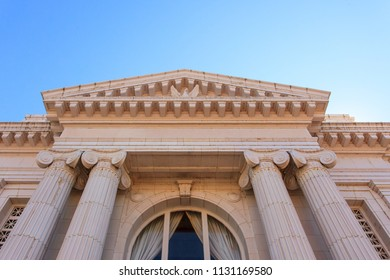 Low angle closeup of a NeoClassical style building with columns and details.