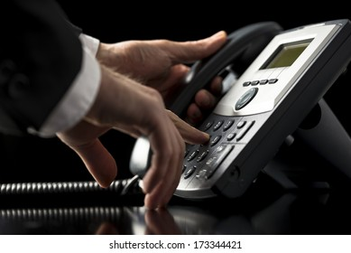 Low angle closeup view of the hands of a businessman in a suit dialing out on a telephone call using a dial-up desktop landline instrument as he presses the numbers on the keypad