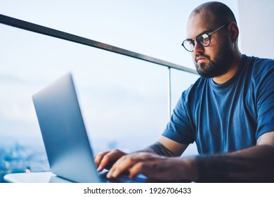 Low angle of concentrated bearded male worker in casual t shirt sitting at table with opened laptop while working in light workspace