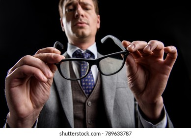 Low angle of confident stylish businessman is standing and frowning while looking at eyeglasses in his hands with concentration. Isolated background. Selective focus