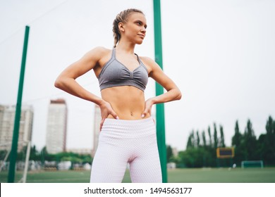 Low angle of confident young blond woman in sportswear standing with arms on waist and demonstrating slim body on urban blurred background and looking away