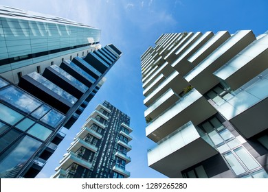 Low angle converging perspective of modern Milan skyscrapers with large balconies against a clear sunny blue sky