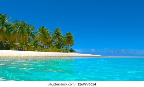 LOW ANGLE, COPY SPACE: Crystal clear ocean water rolls past the beautiful white sand shore of untouched One Foot Island. Spectacular view of the turquoise ocean and an idyllic empty sandy beach.