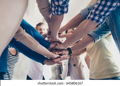 Low angle cropped view of colleagues putting their hands on top of each other, wearing casual clothes. Concept of successful teambuilding and unity