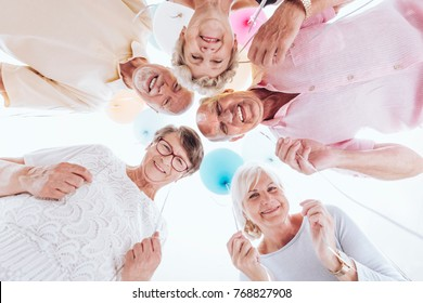 Low angle of elderly friends standing in a circle, have fun together during a meeting