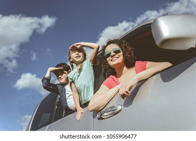 Low angle of excited mother looking over the window while sitting in car. Her son and daughter are covering eyes by hands from sunshine and smiling while viewing the sky