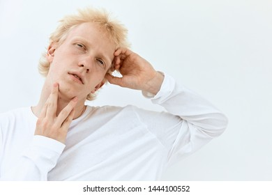 Low angle Fashion portrait of Young albino guy model with blonde hair posing and gesture against white background