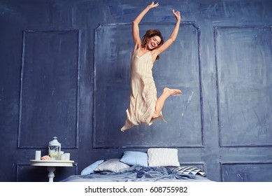 Low angle of a female in the air. Young excited woman jumping on bed. Woman having fun in the bedroom