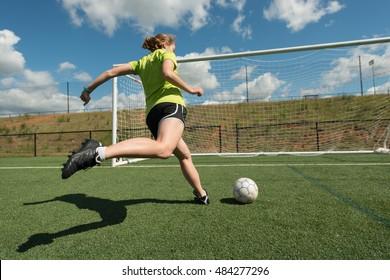 Low angle of female soccer player shooting the ball at the goal with a clear shadow on the turf