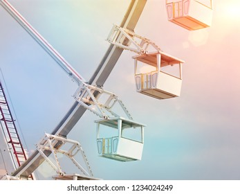 Low angle of ferris wheel view against blue sky background.