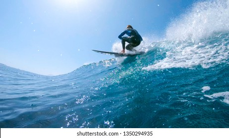 LOW ANGLE: Fit male tourist riding a big blue barrel wave during his active summer vacation in the beautiful Canary Islands. Cool shot of a young man surfboarding on a perfect sunny afternoon in Spain