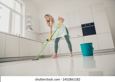 Low angle full length body size view portrait of her she nice attractive focused wavy-haired lady making professional cleanup easy fast comfort service in light white interior kitchen