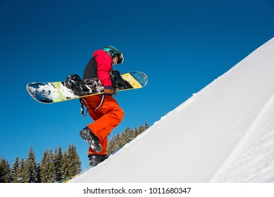 Low angle full length shot of a professional snowboarder walking up the slope in the mountains, carrying snowboard at ski resort on a beautiful sunny winter day copyspace outdoors lifestyle concept