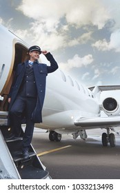 Low angle full length side view happy aviator situating near exit of airplane. Occupation concept