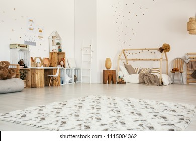 Low angle of a girl's bedroom interior with a patterned rug, wooden desk and shelves, house bed and toys