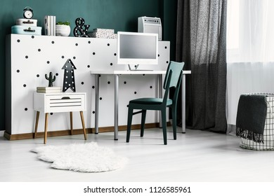 Low angle of green chair at desk with computer monitor in modern bright home office interior