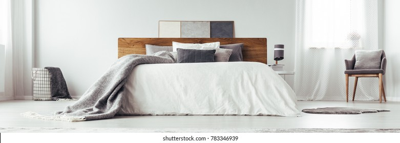 Low angle of grey patterned blanket on white king size bed in bright bedroom interior with grey chair, rug and lamp on nightstand