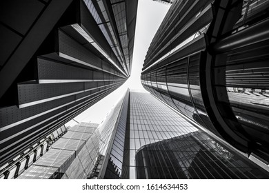 A low angle greyscale of modern skyscrapers with glass windows under sunlight