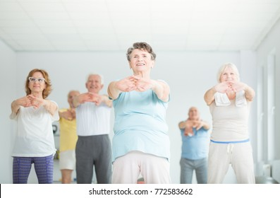 Low angle of group of athletic senior people stretching in a fitness studio
