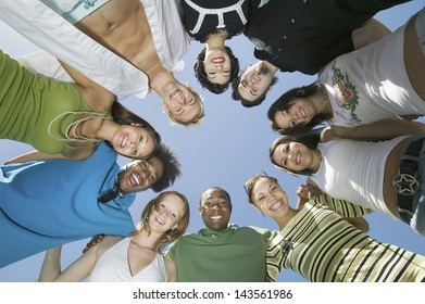 Low angle group portrait of young multiethnic friends in circle against the sky