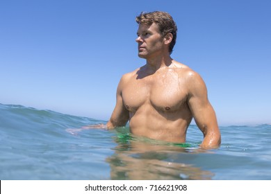 Low angle handsome muscular man wading in open sea on sunny day while observing the scenery