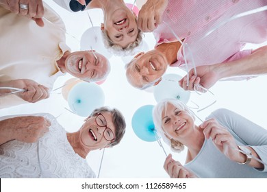Low angle of happy senior people in the circle with balloons during party