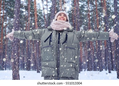 Low angle of happy and smiling woman looking at the sky while standing in the forest. Winter is coming. Having fun on a cold sunny day. Catching snowflakes in winter