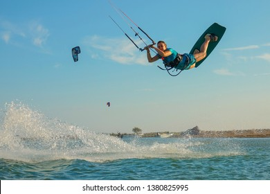 LOW ANGLE: Happy young woman jumps high in the air while kiteboarding in Greece. Fit Caucasian girl catches a strong wind and jumps over the camera during a cool summer kitesurfing trip in Lefkas.