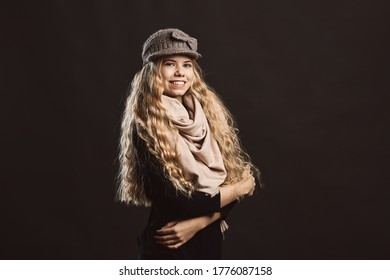 Low angle of happy young woman in stylish black jacket and gray knitted hat and beige scarf looking at camera and smiling while standing with arms crossed against black background in studio