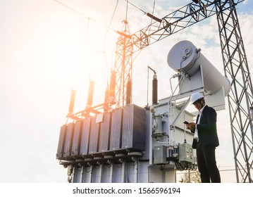 A low angle image of a businessman wearing a black suit, standing looking at a large power transformer with blue sky to be background, Concept about business people who want to invest in energy.