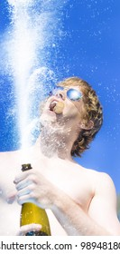 Low angle image of a mans hands holding a champagne bottle with a spray of bubbly and his face above against a blue sky