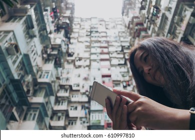 Low angle image of a woman using mobile phone with a crowded residential building in community in Quarry Bay, Hong Kong background