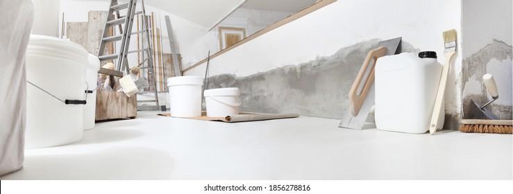 Niedriger Winkel des Innenaufbaus oder der Baustelle der Wohnungsrenovierung mit Werkzeugen auf weißem Boden mit lackierten Eimern und einer Grundiermaschine