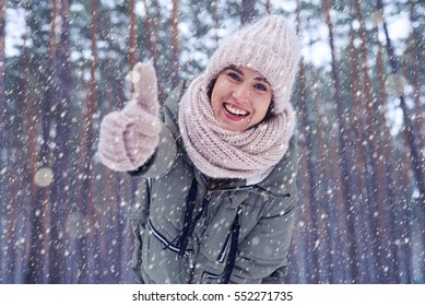 Low angle of joyful female smiling and showing thumb up at the camera. Enchanted winter forest. Woman wearing winter clothes outdoors