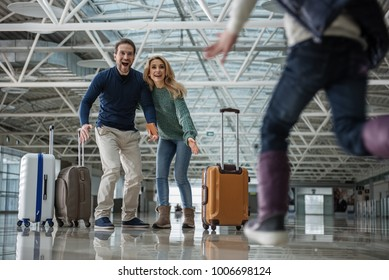 Low angle of joyous kid meeting lovely mother and father at the airport. Girl is running towards them