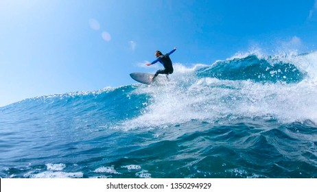 LOW ANGLE, LENS FLARE: Cheerful surfer riding big foaming ocean wave in sunny nature. Stoked man having fun surfing a large wave on his cool surfboard in the summer sun near the idyllic Canary Islands