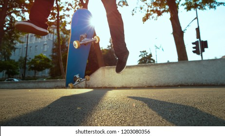 LOW ANGLE, LENS FLARE, CLOSE UP: Unknown skateboarder jumps and lands a cool trick while riding on concrete sidewalk in sunny city. Cinematic view of skateboard flipping in air underneath man's feet.