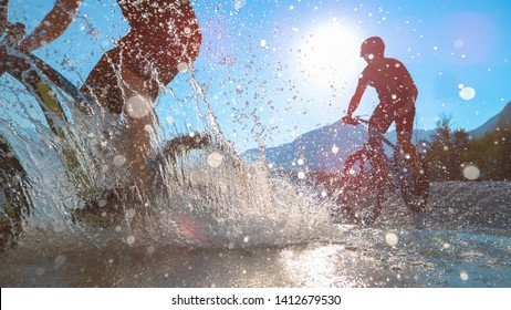 LOW ANGLE, LENS FLARE, SILHOUETTE: Friends spraying water at camera while riding bicycles in Soca river on a beautiful summer day. Two athletic guys riding electric bikes in shallow stream water.