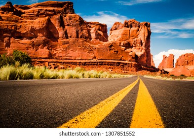 A low angle look down the highway traveling America through Arches National Park with a view of the red rocks and blue sky