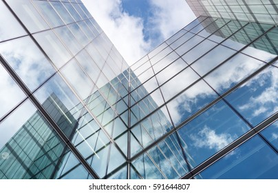 Low angle looking up at tall corporate glass buildings.