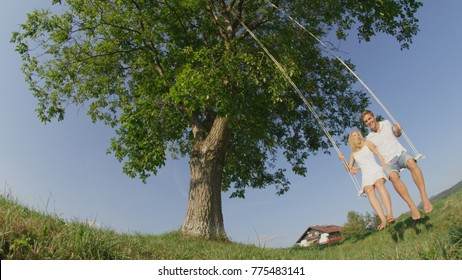 LOW ANGLE: Loving couple swaying on a fun wooden rope swing on summer day. Smiling girlfriend gazing at happy boyfriend, enjoying their date in nature swinging under a large tree in sunlit countryside