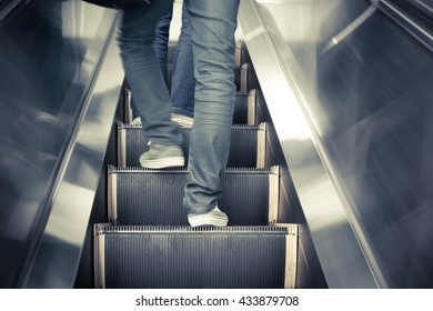 Low angle male feet walking in sneakers up escalator vintage style.