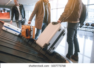 Low angle male friends putting luggages while standing in airport. Journey concept