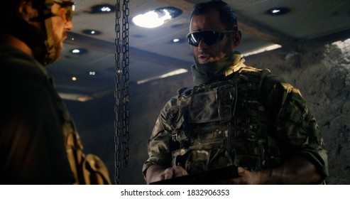 Low angle of man speaking with commanding officer using tablet while planning battle in dark room