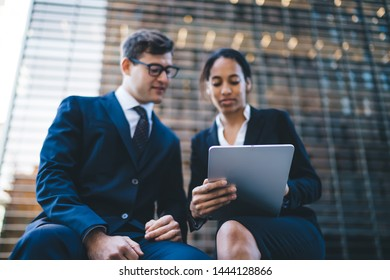 Low angle of modern young multiethnic woman and man sitting together on bench and using tablet against modern building exterior